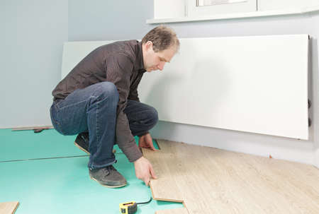 Guy installing laminate flooring indoors photo