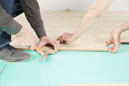 Men hands at flooring installation process photo