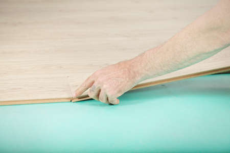 Man hand installing laminate flooring plank photo