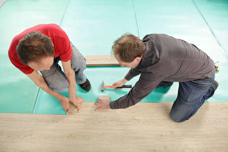 Two men installing laminate flooring indoors