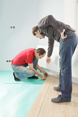 Man instructing worker while installing laminate flooring photo