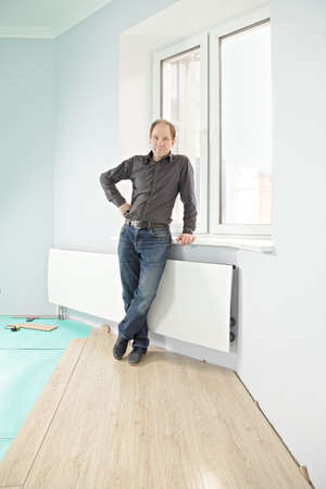 Serious guy standing on new flooring at window photo