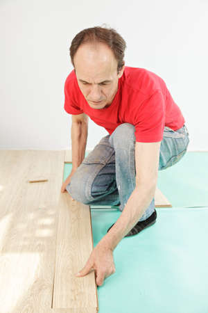 Man in red shirt installing laminate flooring photo