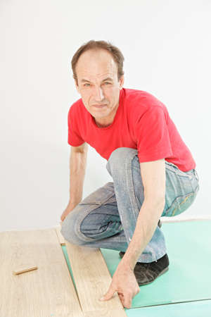 Positive man in red shirt installing laminate flooring photo