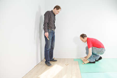 Man with hammer looking at  flooring installation photo
