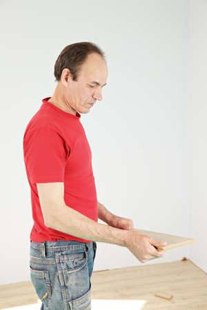 Guy in red shirt holding laminate plank photo