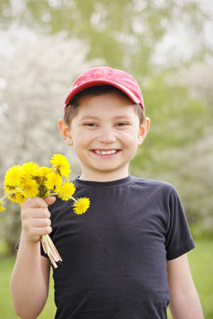 Smiling kid with bunch of dandelions outdoors photo