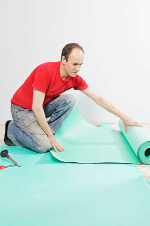 subflooring: Guy in red examining sub-flooring mat