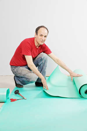 Positive guy in red shirt with sub-flooring mat Stock Photo - 13568488