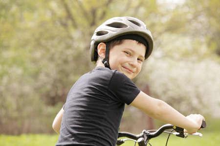 ni�os en bicicleta: Muchacho sonriente en bicicleta mirando por encima del hombro