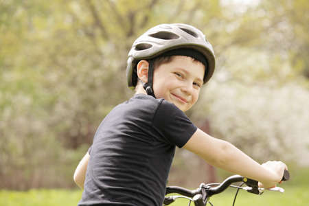Smiling boy on bike looking over shoulder photo