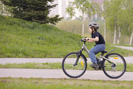 Boy cycling in park sideview photo