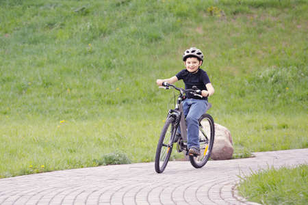Smiling boy cycling in park against green hill photo