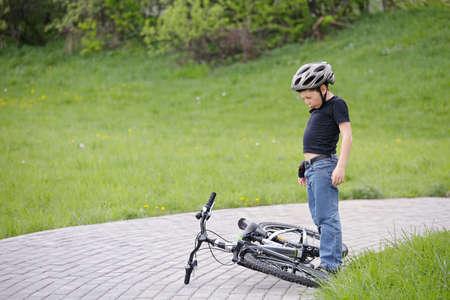 eyes closing: Los ojos del muchacho de cierre y de pie encima de la bici