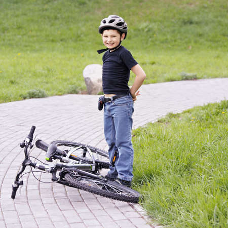 Smiling boy standing over bike in park photo