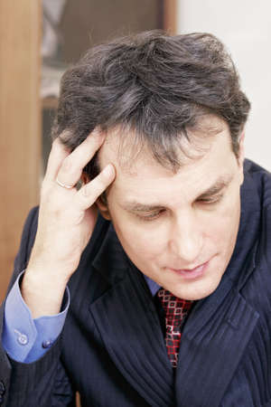 Businessman in stress leaning on hand closeup photo