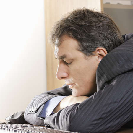Middle aged man sleeping on workplace photo