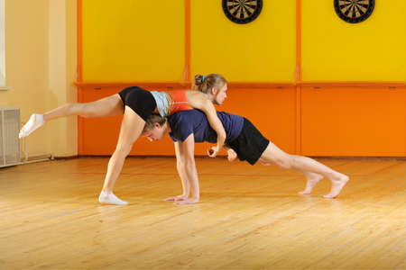 Couple training acrobatics in gym photo