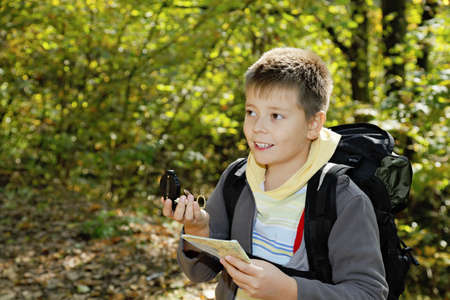 Smiling boy with compas and map orienteering in forest