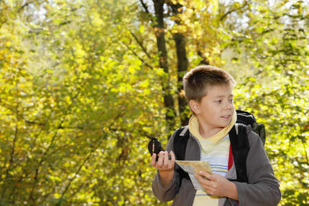 Boy with compas and map orienteering in forest looking sideways photo