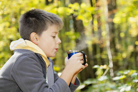 Boy cools hot tea while sitting in autumn forest photo