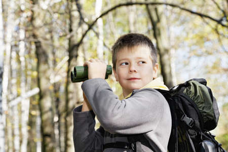 Boy with binoculars in autumn forest looking sideway photo
