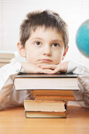 weariness: Chico aburrido sentado en la mesa y se inclina en la pila de libros