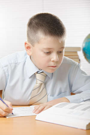 Boy in blue shirt writing at desk while looking at book photo