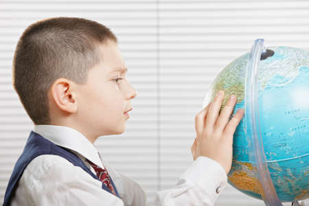 Schoolboy in white shirt with globe side view Stock Photo - 15228403