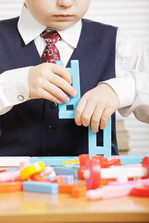 Boy with toy blocks standing at desk closeup photo photo