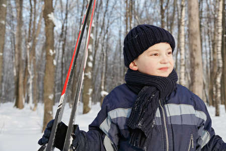 looking sideways: Boy with skis standing in winter in forest looking sideways