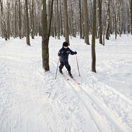 Boy running on skis in winter forest photo