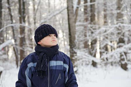 looking sideways: Boy in winter forest looking sideways