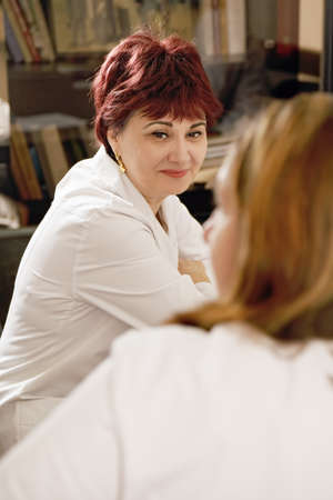 Smiling redhead doctor looking at colleague photo