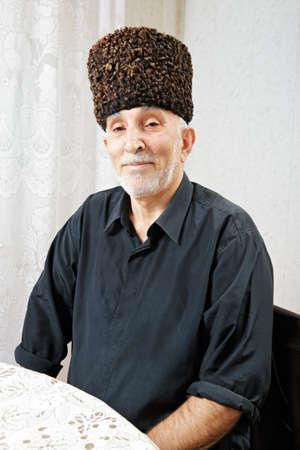 grayness: Senior man in sheepskin hat sitting at table