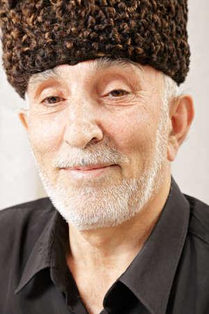 grayness: Portrait of senior man in sheepskin hat