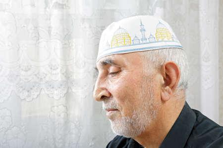 grayness: Senior man in religious hat profile view portrait