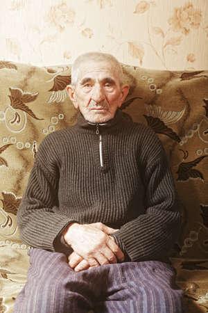 grayness: Senior man sitting on sofa hands folded Stock Photo