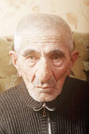 hoariness: Senior man sitting on sofa closeup portrait