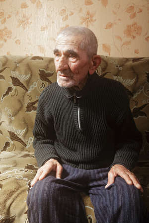 grayness: Senior man sitting on sofa looking sideways Stock Photo