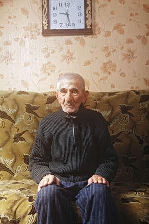 hoariness: Senior man sitting on sofa under clock