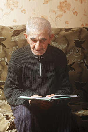 Senior man reads book while sitting on sofa photo