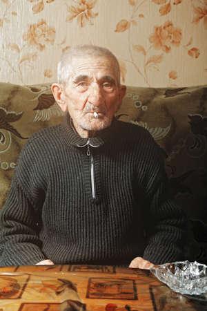 grayness: Senior man smoking while sitting on sofa at table Stock Photo