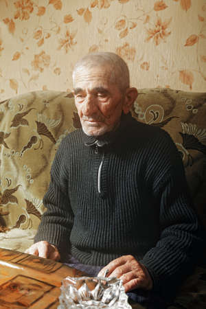 grayness: Thoughtful man with cigarette sitting on sofa indoors
