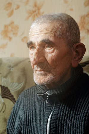 looking sideways: Portrait of senior man sitting on sofa looking sideways Stock Photo