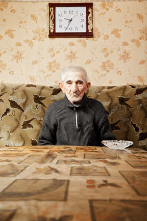 Senior man sitting at table under wall clock photo
