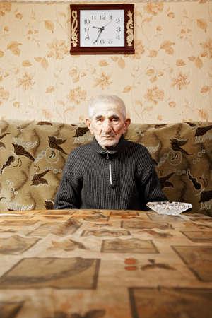 grayness: Senior man sitting at table under wall clock
