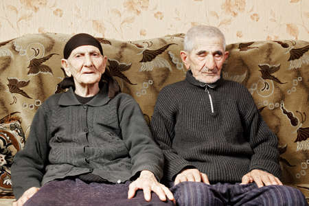 Senior couple on sofa woman looking to camera while man sitting with eyes closed photo
