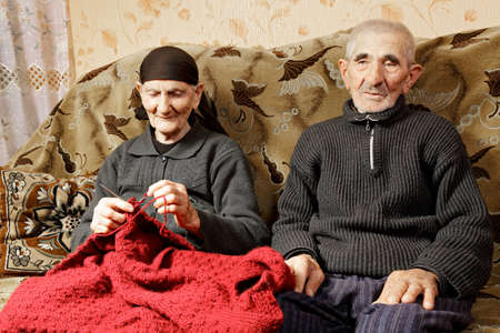 grayness: Senior couple sitting on sofa woman knitting while man looking sideways Stock Photo