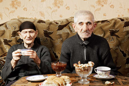hoariness: Senior couple drinking tea at table sitting on sofa